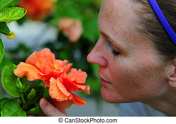 Pretty woman smelling flowers