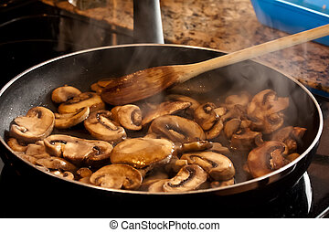 Sauteed Mushrooms - mushrooms frying in a pan on the stove