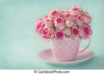 Pink roses in a cup on blue background
