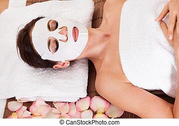 Beautiful young woman getting facial mask