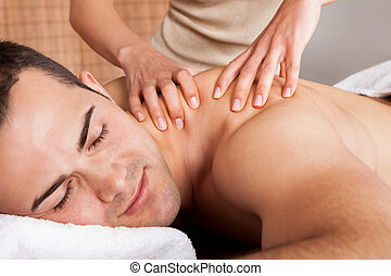Young man getting shoulder massage - Cheerful young man...