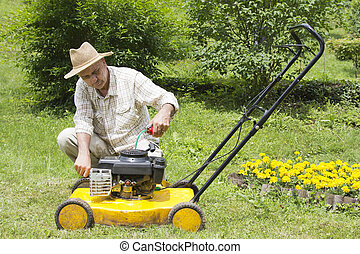 Mid age man repairing lawn mower - Mid age man oiling and...