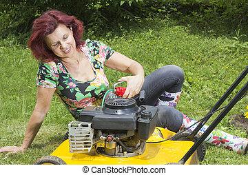 Smilling women oiling lawn mower