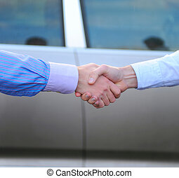 handshake between two men on the background of the car