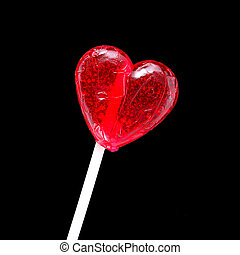 Red heart-shaped lollypop shot over black background