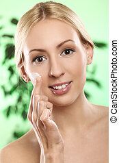 Woman applying moisturizer cream on the face - Beautiful...