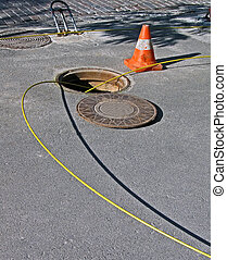 open manhole with few yellow optic cables under sunny...