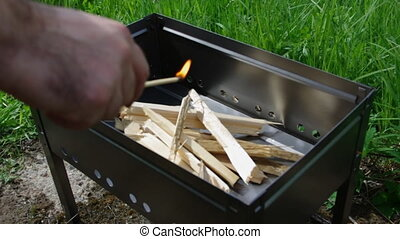 Making fire wood .lighting BBQ wood with match.