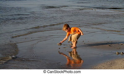 Boy Digging In Sand - Young boy digs in the sand at the...