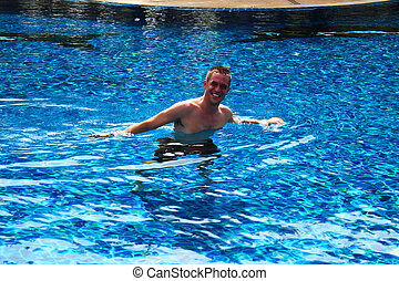 Man swimming in a pool in Thailand.