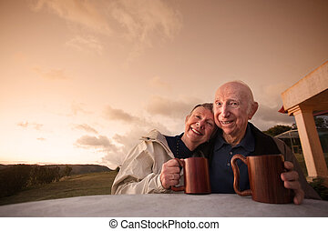 Happy Mature Couple - Happy mature couple at table outside...