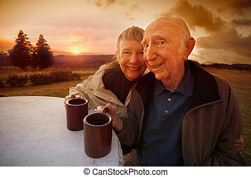 Happy Senior Couple at Sunset - Happy senior couple drinking...