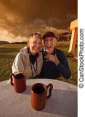 Laughing Elderly Couple - Cute elderly couple at table in a...