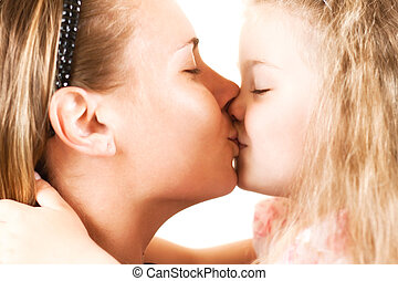 girl kissing her mother - the little girl tenderly kisses...