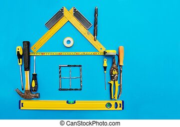 Tools in the shape of house over blue background. Home...