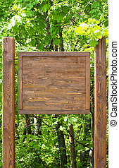 Wooden sign - Brown wooden sign on the green forest...