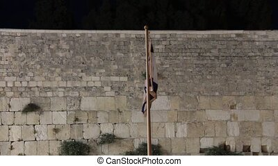 State flag of Israel at the night on Western Wall background