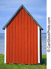 Boathouse - Red boathouse with blue sky and water in...