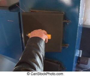 hand open boiler door. fire burning inside. boiler fired...