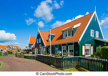 Typical dutch houses reflected in water on a sunny spring...