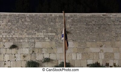 State flag of Israel at the night on Western Wall background...