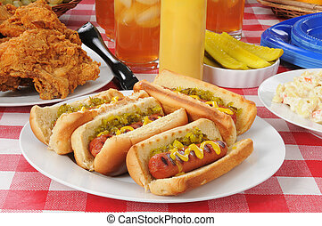 Grilled hot dogs and fried chicken on a picnic table
