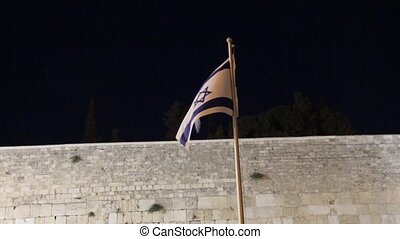 State flag of Israel against the background of the Wailing...