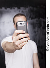 Klick for photo! - Man with mobile phone, background is...