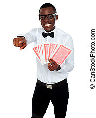 Gambler with playing cards pointing at you isolated over...