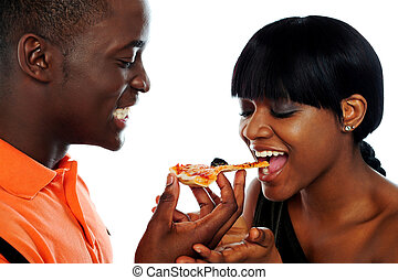 Beautiful african couple eating pizza isolated over white,...