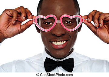 Smiling man wearing heart shaped eye-wear. Love and funny...