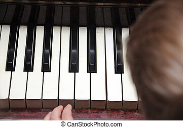 A cute baby plays with a piano.