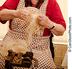 Elderly woman spinning wool - Photo of a elderly woman that...