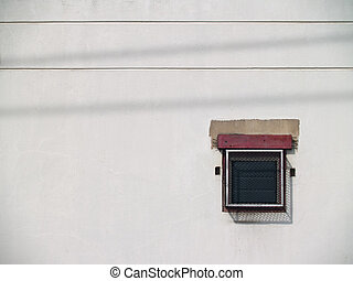 Small window with louver and grid on old white wall