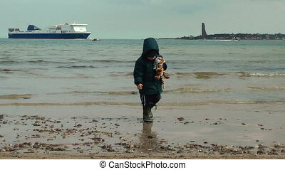 Little boy playing on the beach with huge ferry on the...