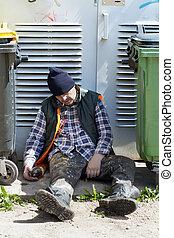 Tramp sleeping near dumpsters