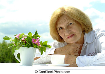 Beautiful Caucasian elderly woman sitting with a flower on...