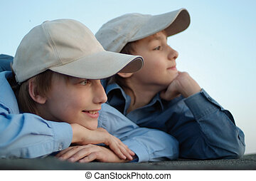 Two Caucasian brother sitting in the caps on the street