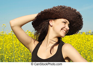 Beautiful Caucasian woman in a hat lying in the grass