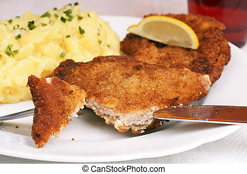 Wiener Schnitzel with potato salad topped with chopped...