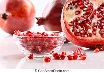 Pomegranates with bowl of seeds - Ripe pomegranates and...