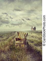 Old sofa chair in tall grass on prairie path