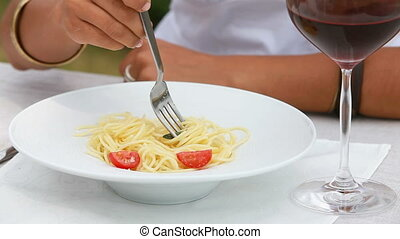 Lunch outdoors - Close-up of a female eating spaghetti and...