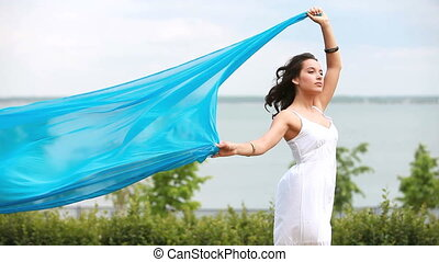 In the wind - Romantic girl holding a piece of light blue...
