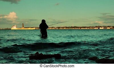 Fisherman in water at sunset, Laboe coastline, Kiel, Germany