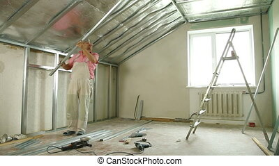 House Renovation - Man installing plasterboard walls in the...