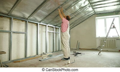 Installing drywall - Man installing drywall on ceiling