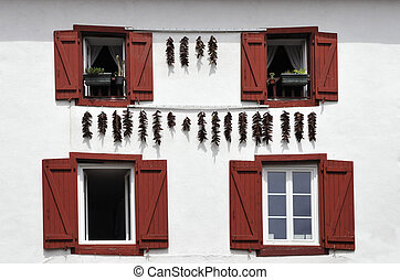 Red Spices hanging on a White Wall with Red Shutters - Red...