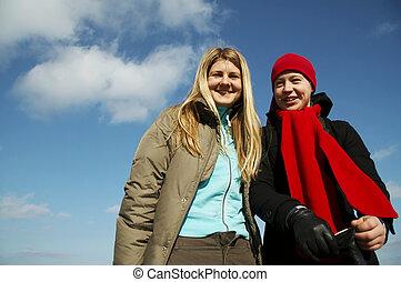 Girlfriends - Two joyful girls on blue background