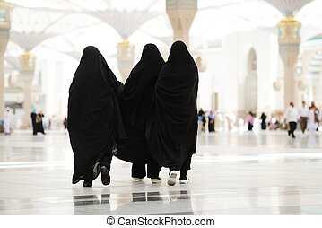 Three Moslim women walking outdoors - Islamic Holy Place